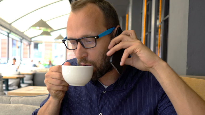 Young man talking on cellphone and eating sandwich in cafe | Shutterstock HD Video #1033546034