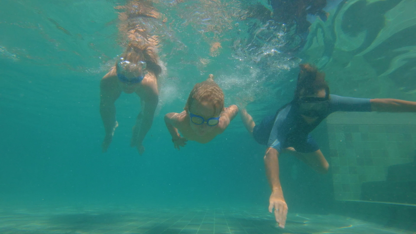 Slowmotion underwater shot of a happy family diving in a swimming pool. Healthy lifestyle, active parents #1033553771