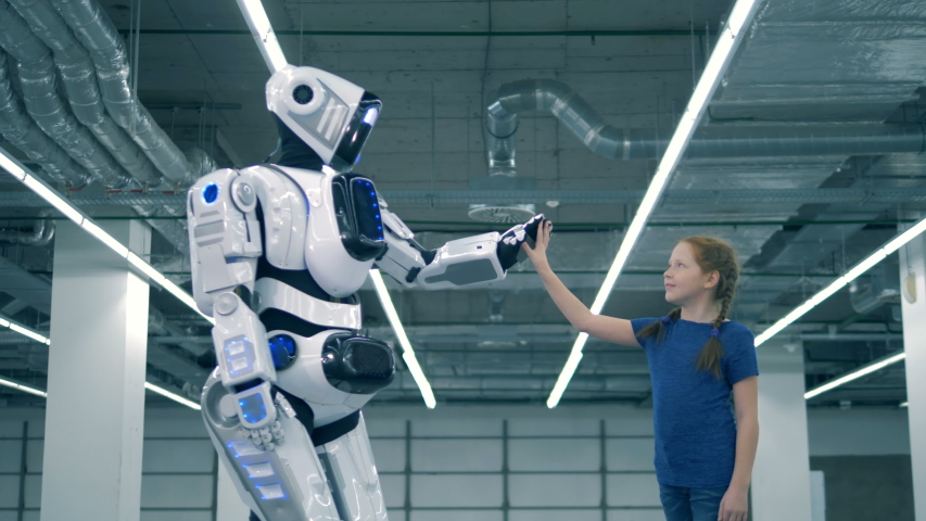 A robot and a girl touching hands, side view. School kid, education, science class concept. | Shutterstock HD Video #1033569722