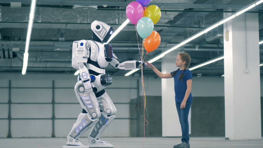 White android gives colorful balloons to a girl, side view. | Shutterstock HD Video #1033569767