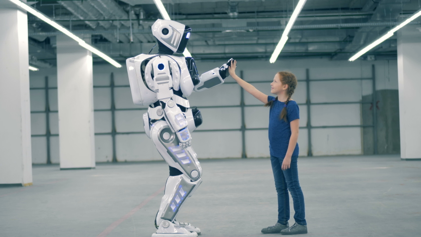 A droid and one girl touching hands, side view. | Shutterstock HD Video #1033569770
