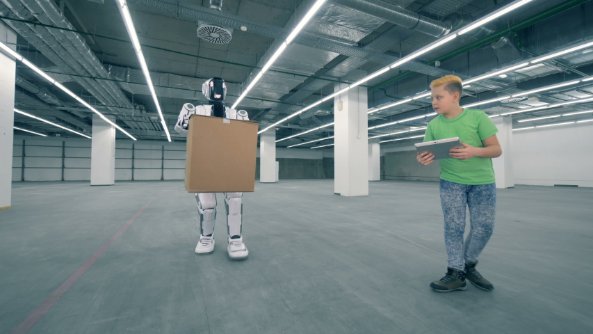 A cyborg lifts a box while a boy controls it. | Shutterstock HD Video #1033569779