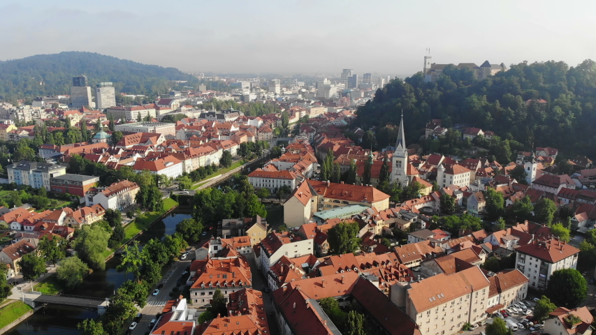 Aerial view of Ljubljana, Slovenia. Ljubljanica river, Ljubljana castle and old town. Summer morning haze, drone video. Royalty-Free Stock Footage #1033570877