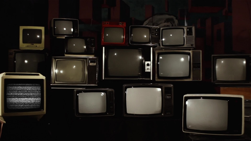 "Retro TV Turning On Green Screen over a Pile of Retro TVS from the 80s and 90s. You can replace green screen with the footage or picture you want. You can do it with ""Keying"" effect in After Effects. 