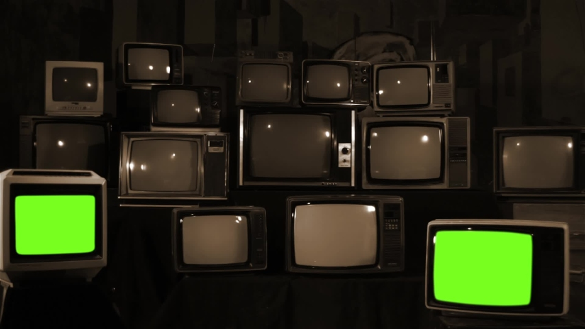 "Two Retro TV Turning On Green Screen over a Pile of Retro TVS from the 80s and 90s. You can replace green screen with the footage or picture you want. You can do it with ""Keying"" effect. 