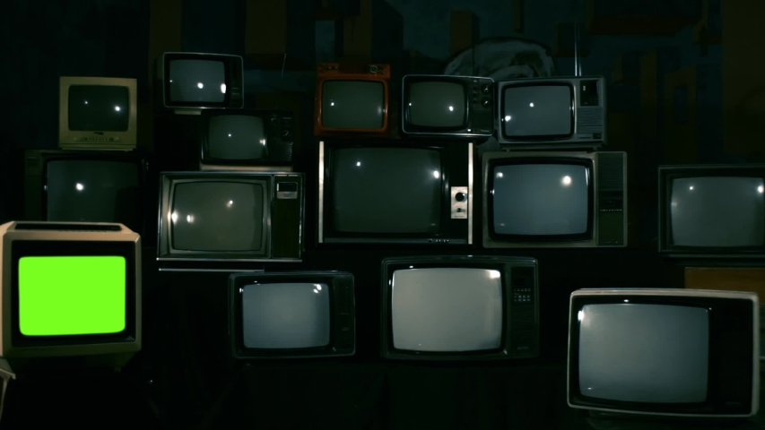 Retro TV Turning On Green Screen over a Pile of Retro TVS from the 80s and 90s. Zoom In Shot. Blue Steel Tone.   | Shutterstock HD Video #1033573283