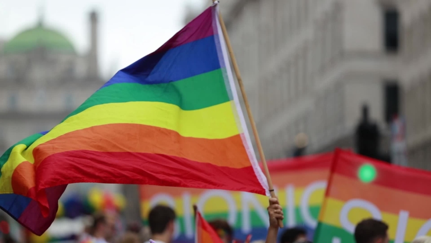A LGBT gay pride rainbow flag being waved at a pride march celebration event