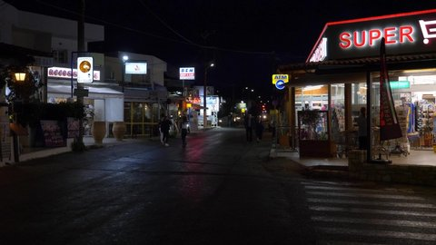 Sissi, Crete - July 19, 2018: Night view of the streets near the harbor with shops and traffic and tourists