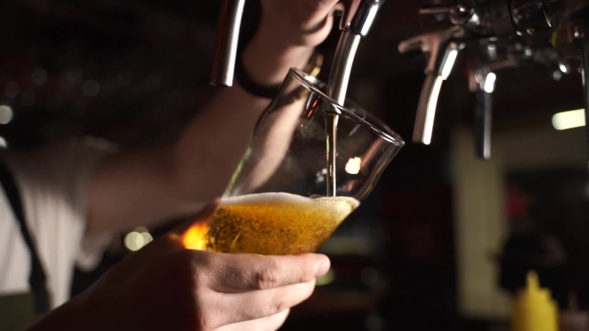 Bartender pouring beer into glass with bubbles close up