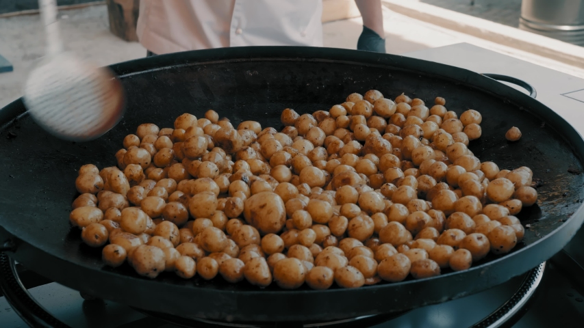 Chef Prepares Potatoes Fries on a Large Skillet in a Street Restaurant | Shutterstock HD Video #1033588496