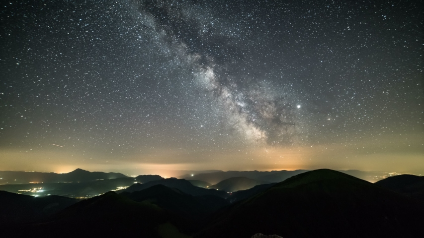 Starry night in mountains Time lapse. Milky way galaxy stars moving over countryside traffic. Night to day