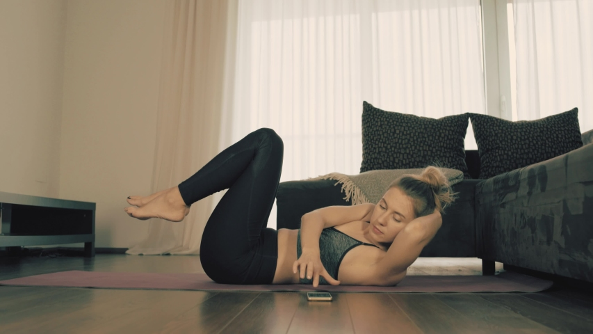 Young woman doing sports at home, Female fitness training in sportswear in the room    Shutterstock HD Video #1033597847