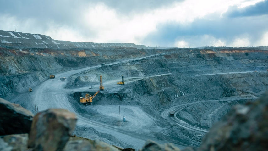 Work of trucks and the excavator in an open pit on gold mining, timelapse, soft focus