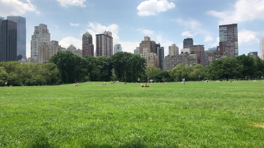 NEW YORK CITY crowd on a sweltering hot summer day in Central Park in New York. Central Park is a public park at the center of Manhattan that opened in 1857, on 778 acres of city-owned land.