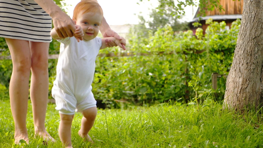 Little cute toddler boy holding his mother's hands and doing first steps barefeet on the grass.