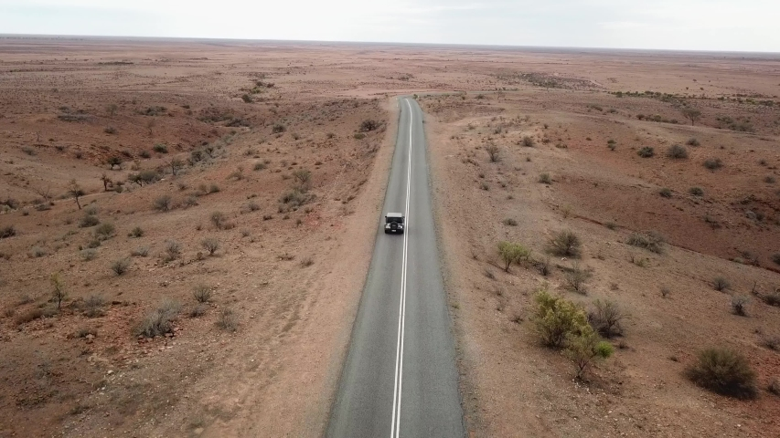 Aerial: Drone shot tracking a vehicle driving down an empty road in the Australian outback towards the horizon near Broken Hill, Australia | Shutterstock HD Video #1033627793