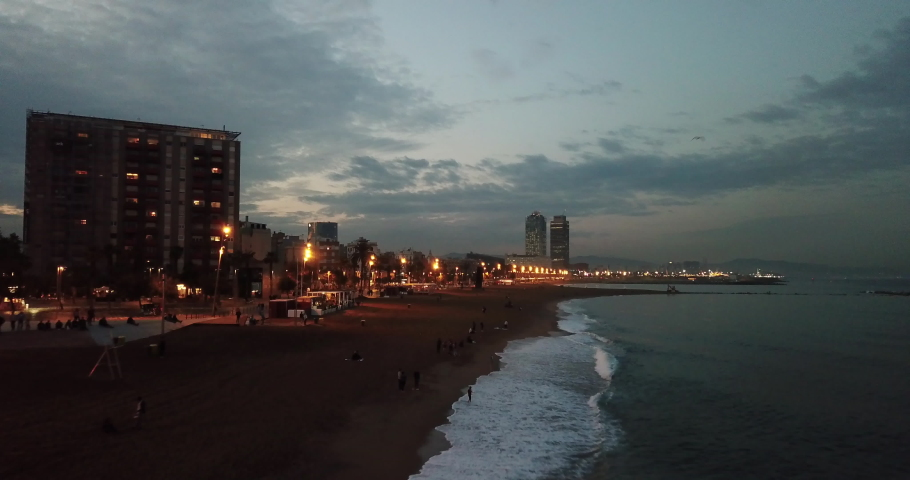 High aerial drone shot flying over beautiful Barceloneta Beach in Barcelona during night.