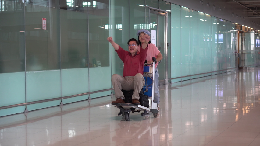 Happy  wife and husband  Having fun on luggage trolley or baggage cart while waiting for departure .Playful asian Senior couple traveling at terminal airport . Elderly Journey. older lovers . travel.