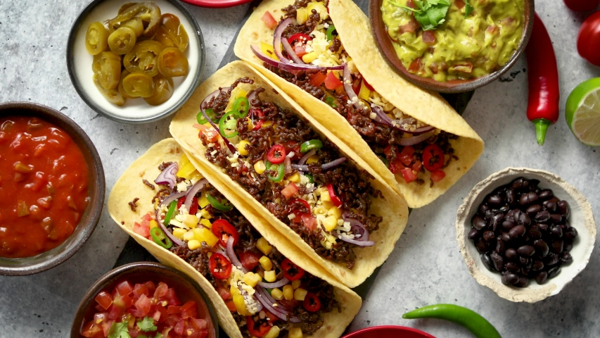 Tasty Mexican meat tacos served with various vegetables and salsa. With sides in ceramic bowls around. Top view composition.