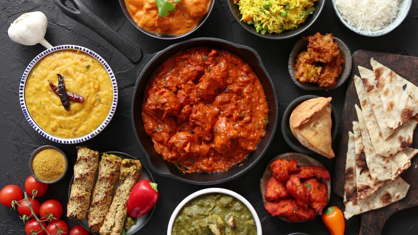 Assortment of various kinds of Indian cousine on dark rusty table. Chicken Tikka Masala, Butter, Nilgiri, Daal Tarka. Served with fried rice, naan bread and spices. Royalty-Free Stock Footage #1033649384
