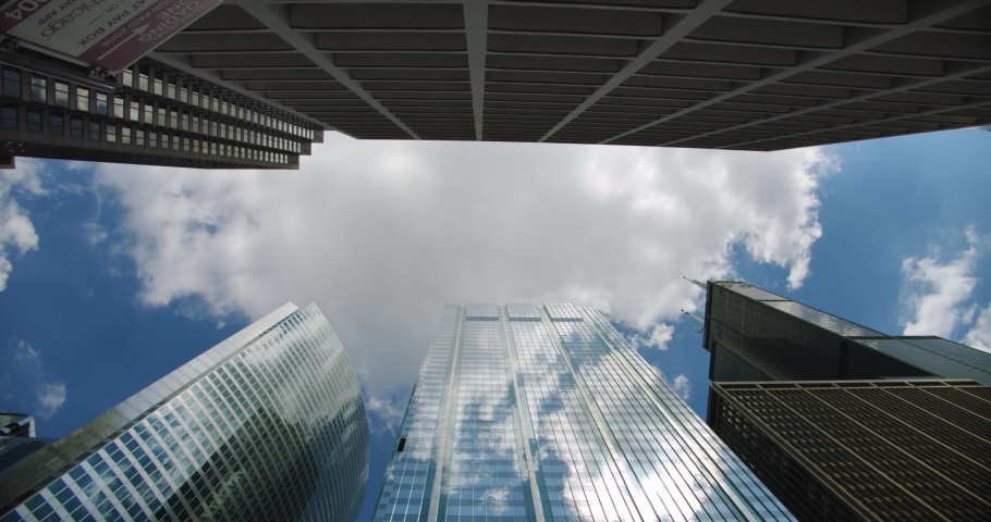 Looking up at skyscrapers business buildings in dowmtown and the plane flies over the city clouds rolling in sky and reflections on glass | Shutterstock HD Video #1033654505