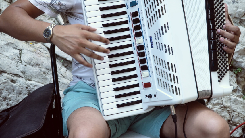Street performer playing Classic muscal instrument, accordian.