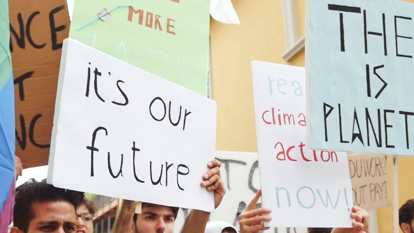 Public demonstration on the street against global warming and pollution. Group of multiethnic people making protest about climate change and plastic problems in the oceans