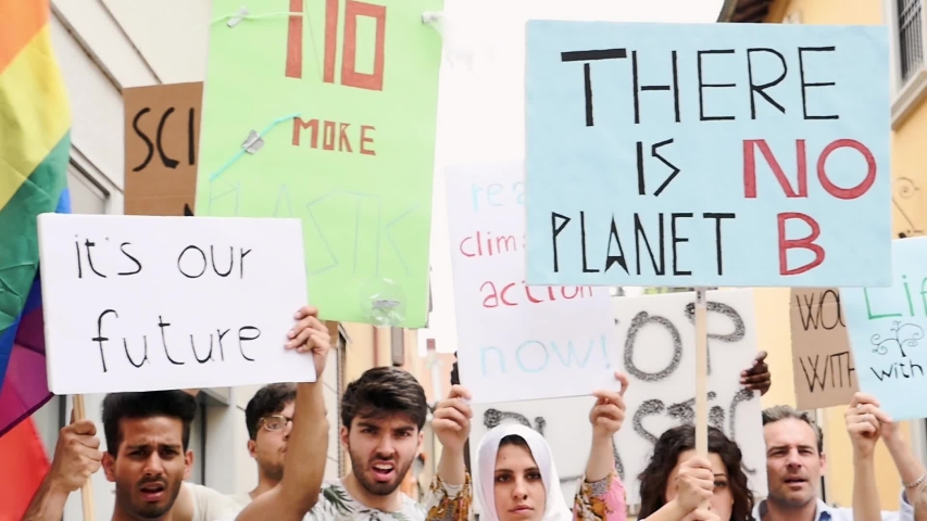 Public demonstration on the street against global warming and pollution. Group of multiethnic people making protest about climate change and plastic problems in the oceans | Shutterstock HD Video #1033661720