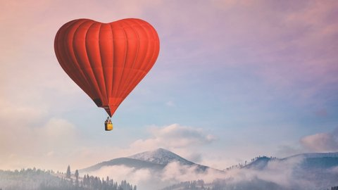 Hot air balloon. Floating Red Heart fly in pastel sunset sky. Foggy mountains in the background. Romantic journey on Valentine's Day. Love, Travel, holidays. Nature landscape. Slow motion 4K