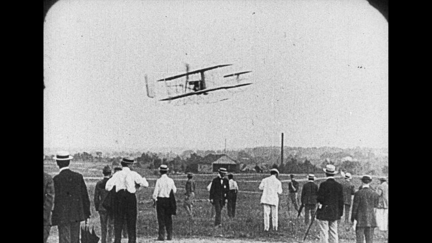 1920s: Two men sit in early Wright brothers plane. Propellers start and slingshot plane down rail to flight. Plane flies in sky then comes in for landing