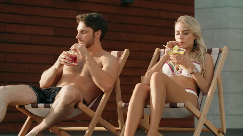 Summer couple drinking cocktails in sun chairs. Close up relaxing couple sitting near pool. Love couple enjoying summer vacation near swimming pool. Sexy woman in bikini having resort relax.