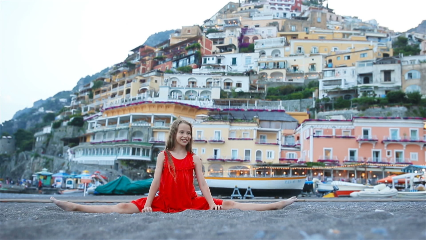 Adorable little girl with Positano view on Amalfi coast at sunset. Sports girl sits in a splits on the sand | Shutterstock HD Video #1033691582