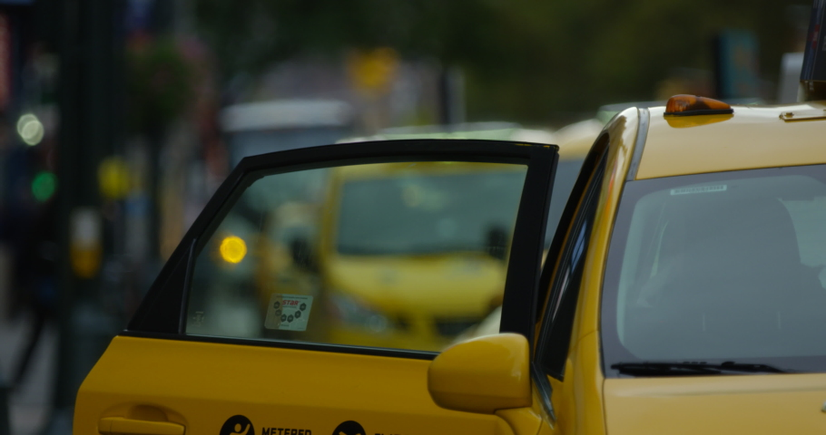 Iconic Yellow New York Taxi Shutting Door Picking Up Passengers and Driving Into the Famous Manhattan NYC On Iconic New York Side Walk. | Shutterstock HD Video #1033708223