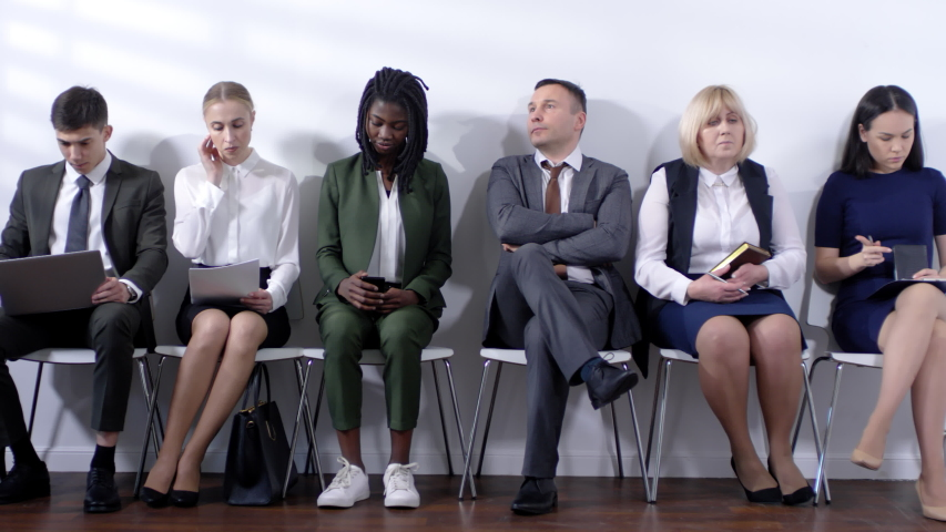 Medium shot of nervous man in suit sitting down on chair and waiting for job interview with group of people in formalwear | Shutterstock HD Video #1033713026