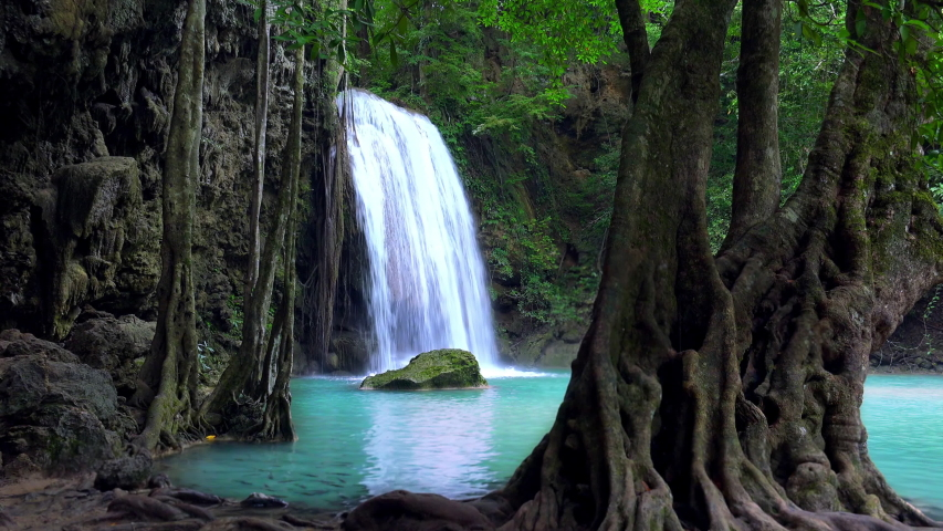 Mysterious magical Erawan cascade waterfall. Kanchanaburi National Park, Thailand. Ancient trees growing in turquoise water. Fishes swimming in azure lake. Tropical paradise. Amazing lush vegetation