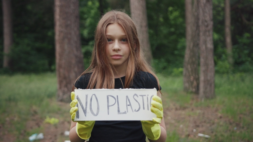 Save the planet for future. Portrait of a sweet teen girl showing a sign protesting against plastic pollution in the forest. No plastic concept. Eco-friendly environment.