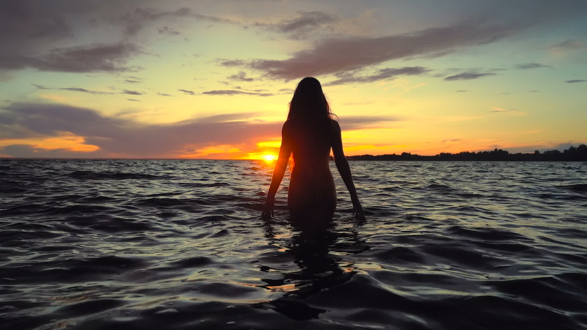 Slim young woman walking in the sea above the sunset sky. Slowmotion. Handheld shot.