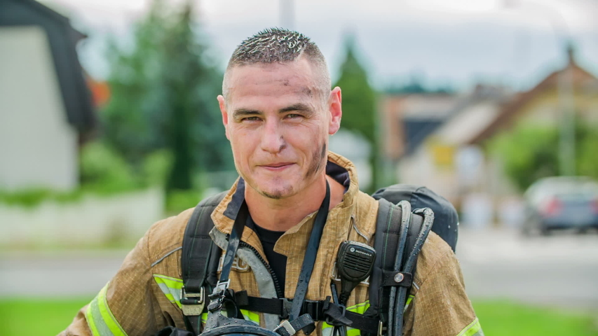 DOMZALE, SLOVENIA - 7. JULY 2018 A firefighter has finished with a firefighting operation. He is wiping his forehead and hair because they're wet.
