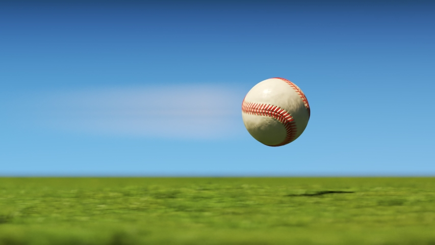 White leather baseball flying fast through the air in slow motion above the freshly-cut stadium grass. Infinite movement in slow motion with motion blur streak.  Clear blue sky on a sunny day.