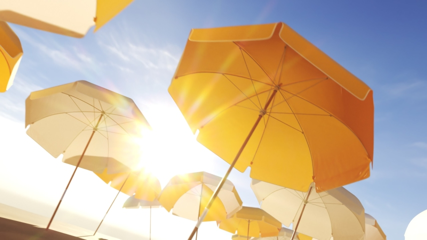Yellow and white beach umbrellas or parasols against blue sky. Seamless looping animation with colorful striped umbrellas during a sunny day on a beach. Symbol of vacations, relax, summer. 4k  Royalty-Free Stock Footage #1033790744