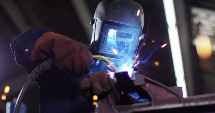 4K Female metalworker in industrial workshop lifting up mask to check her work. Slow motion.