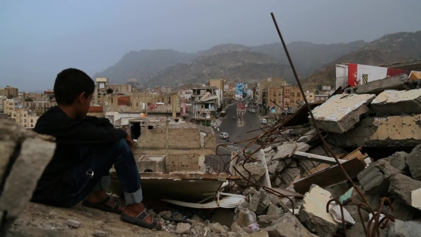A child from Taiz City sits on the ruins of his ruined home because of the war on the city-Yemen.