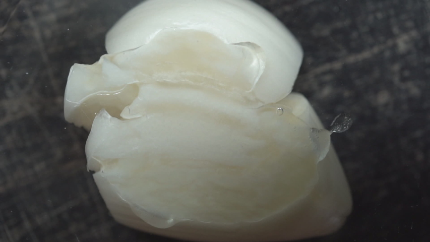 Clove of garlic is crushed on the kitchen table,close-up, slow mo. Men's hands crushing garlic while cooking.Crushing a garlic clove. | Shutterstock HD Video #1033804319