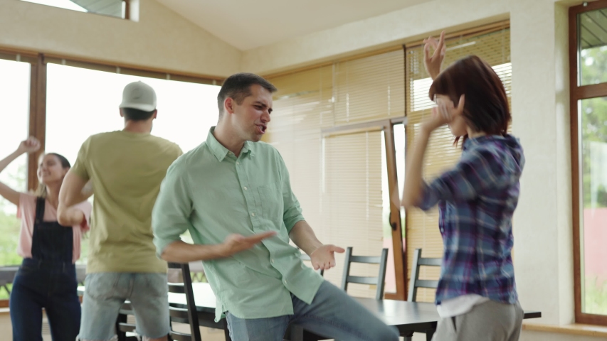 Four energetic diverse friends, two men and two women, enjoying dancing at home party. Young people moving to music together and singing #1033808966