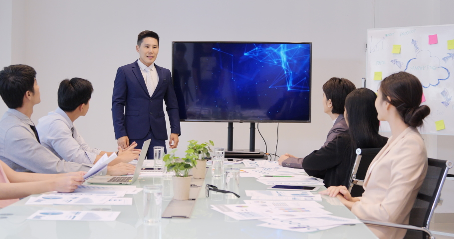 Asian Businessman Presentation to him Business Plan with Team, He Shows Information on the Wall TV. Business concept.