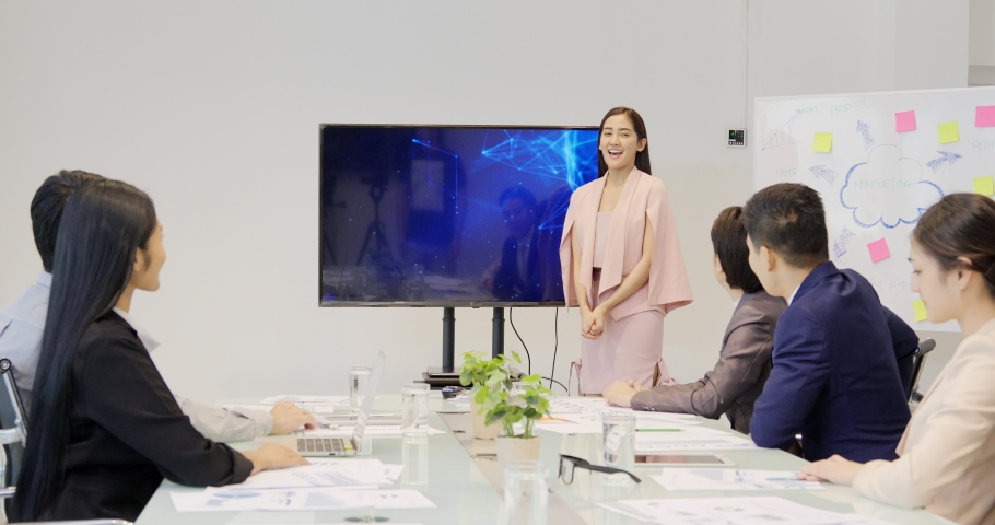 Asian Businesswoman Presentation to Her Business Plan with Team, She Shows Information on the Wall TV. Business concept.