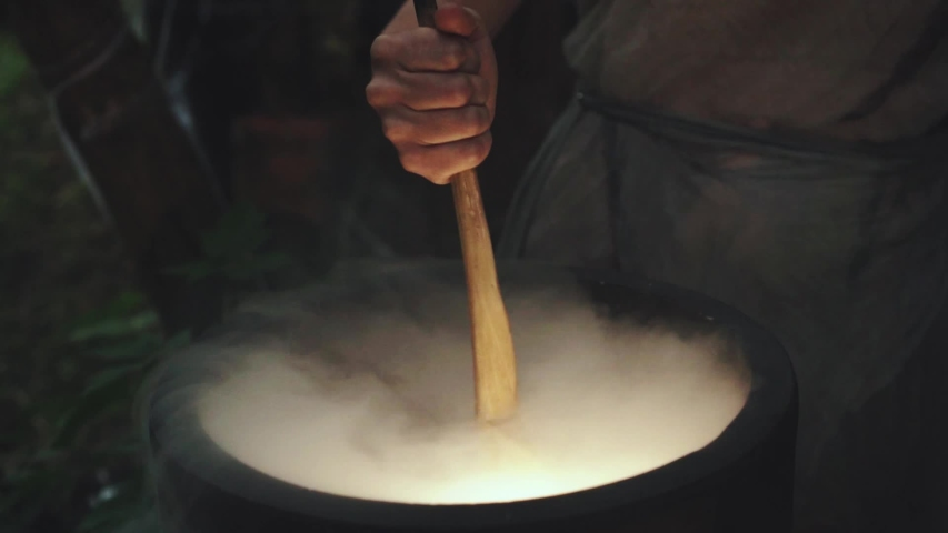 Human hand of old woman evil witch is stirring potion in  bubbling vat pot with wooden spoon. mystery silhouette preparing cooking potion medicine couples spell, curse. Halloween sorceress mage.  | Shutterstock HD Video #1033843076