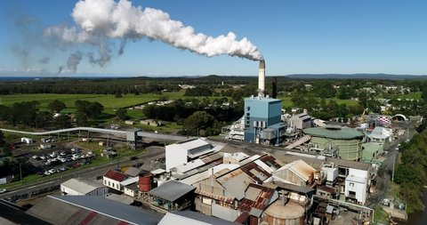 Close view at workshops and industrial machinery around tall chimney of sugar mill plant in Australia during processing of sugar cane.