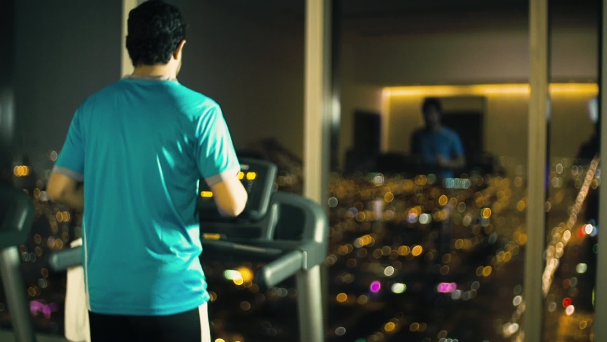 A man playing sport with a city scape in front of him night shot. | Shutterstock HD Video #1033850600