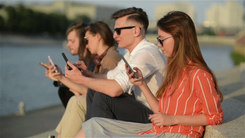 Four Friends Laughing Happy And Watching Social Media In a Smart Phone in The Street. Everyone With His Own Phone. Best Friends and Students Spending Time Together Outdoors. | Shutterstock HD Video #1033857464